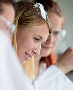 Female chemistry students dressed in laboratory coats and safety goggles.